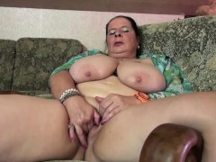 chubby mature lady oiling up her tits and toying her muffin