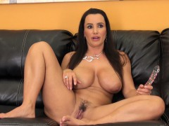 monster tit milf lisa poses on the couch and fingers her wet snatch